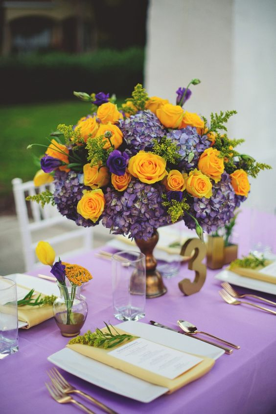 a purple tablecloth, yellow napkins, a bold centerpiece of purple hydrangeas and yellow roses for an exquisite look