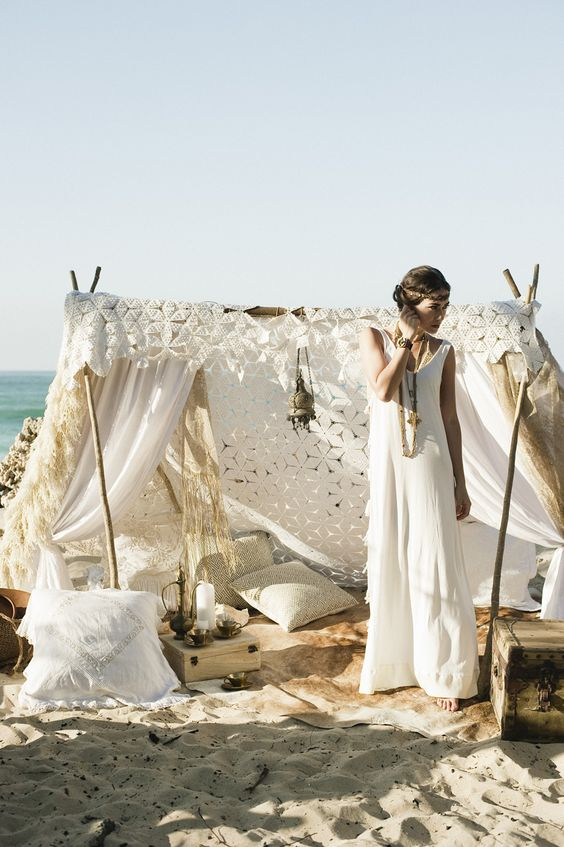 a gorgeous boho wedding teepee with lots of pillows and lanterns for a boho beach wedding