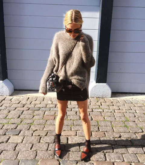 With oversized sweater, mini skirt, flats and bag