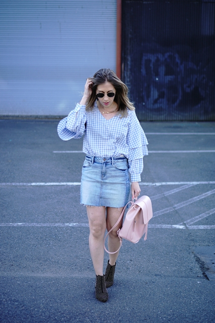 With denim skirt, pink backpack and ankle boots