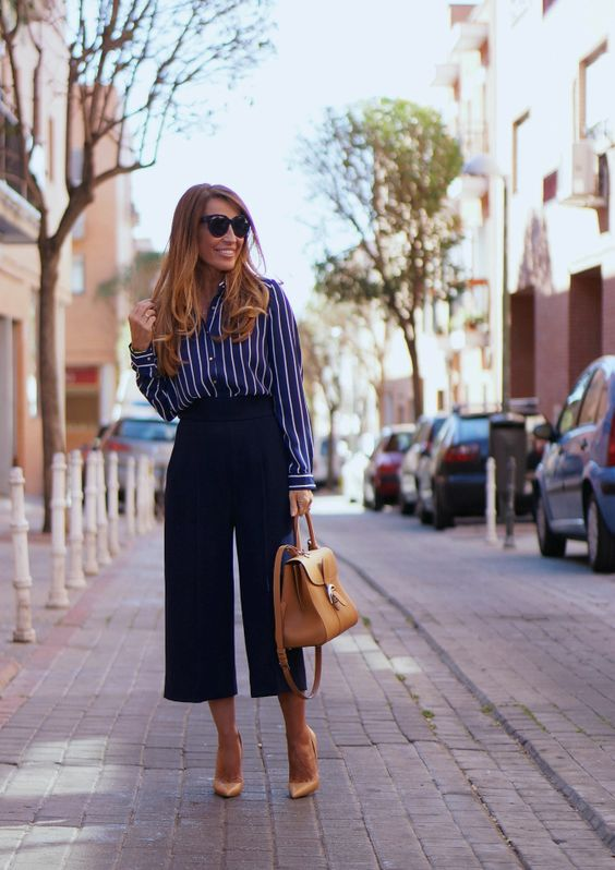navy culottes, a vertical stripe blue and white shirt, tan shoes and a bag