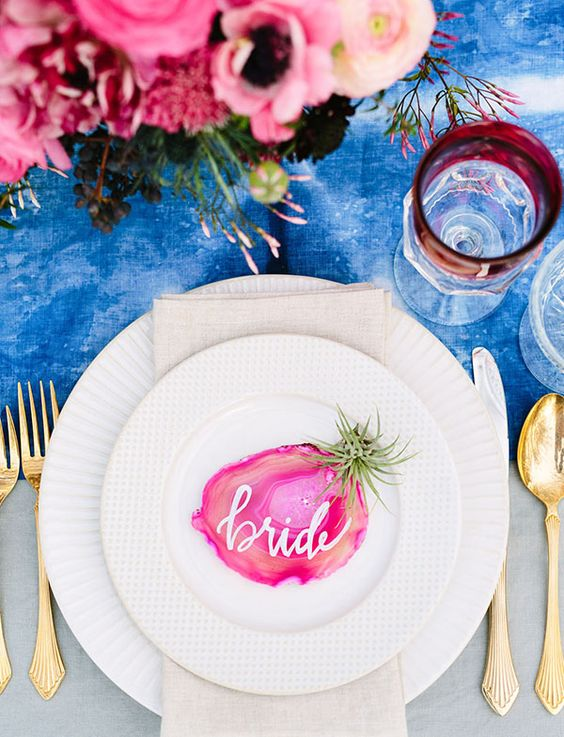 a bold blue watercolor table runner, a bright pink floral centerpiece and an agate slice card