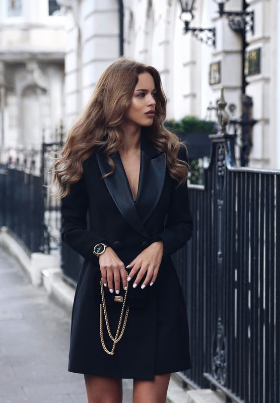 a chic black tuxedo outfit with long sleeves and a double breast, a chic clutch and watch
