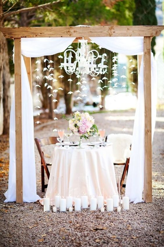 a rustic sweetheart table with an arch and ethereal fabric and paper flowers hanging