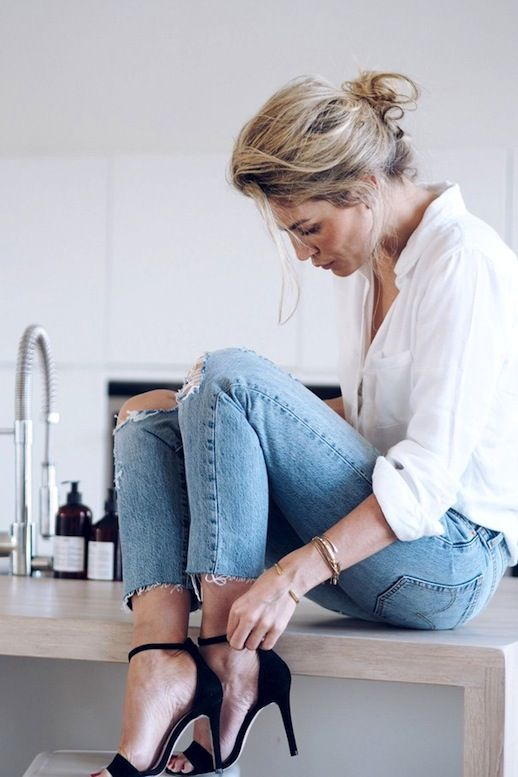 a white shirt, light blue ripped and raw hem jeans and chic black heels