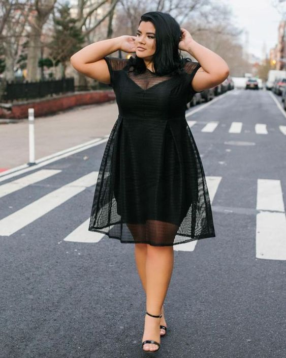 a black knee dress with a sheer overdress, an illusion neckline and trim, black heels