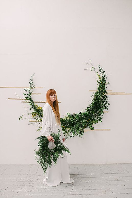 a crescent moon foliage wedding arch with gold tape and green garland for a natural feel