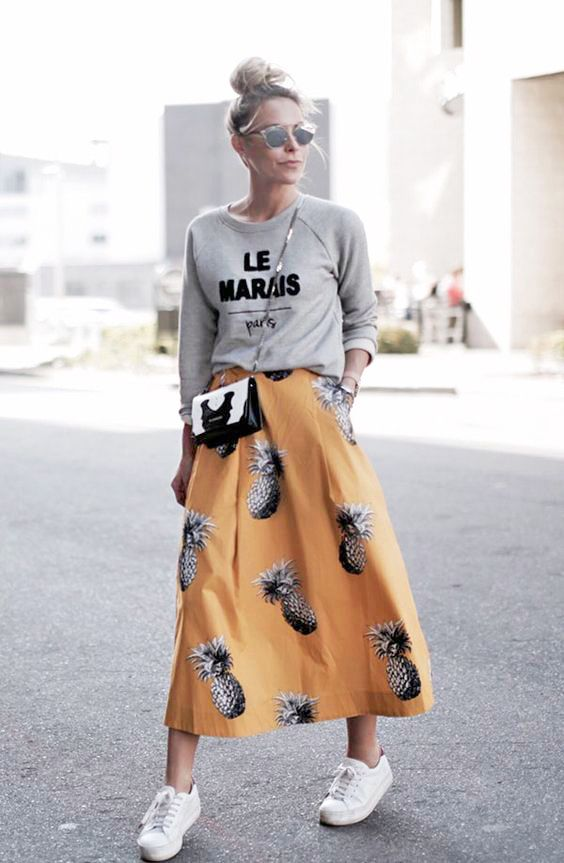 a grey printed sweatshirt, a bold yellow midi skirt with a pineapple print, white sneakers and a crossbody