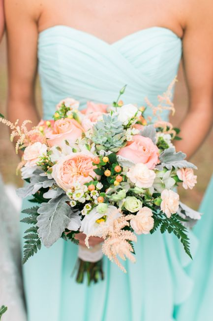 a bridesmaid wearing a strapless mint dress and a peachy pink and pale grey bouquet