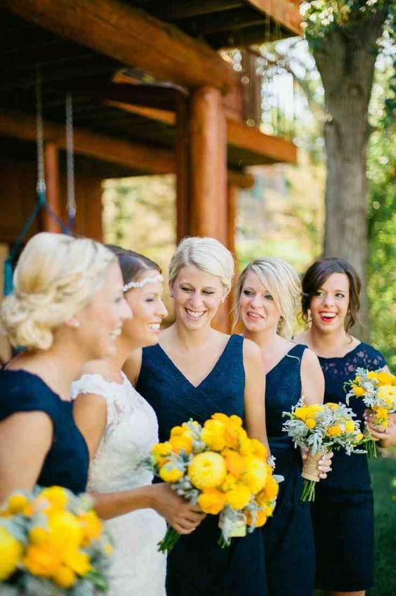 bridesmaids in navy dresses and holding yellow bouquets is a very bold and chic combo to go for