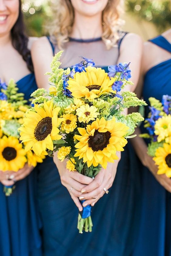 navy dresses and sunflower and delphinum bridesmaids' bouquets for an elegant combo