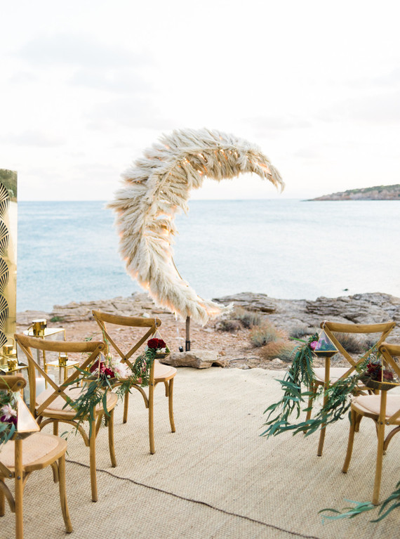 The wedding space was done with chairs with floral terrariums and a jaw-dropping pampas grass wedding altar shaped as a crescent moon