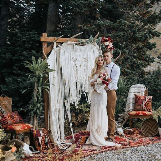 a bold ceremony space with a macrame wedding arch, rugs, pillows and antlers