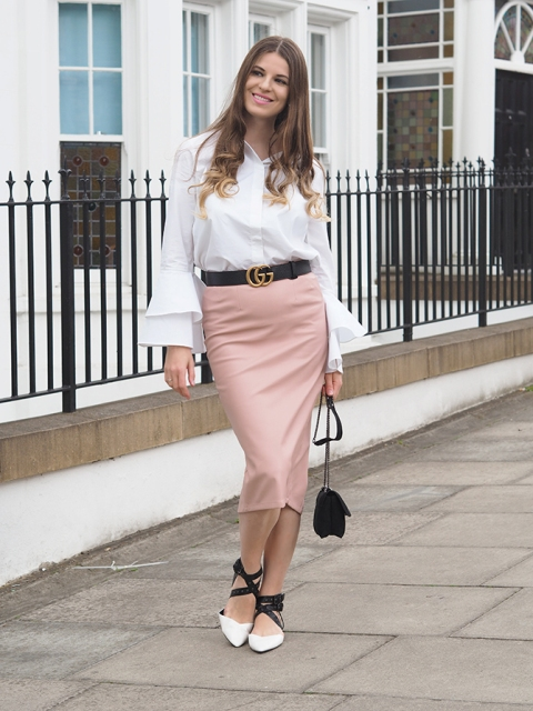 With pale pink skirt, black and white shoes and mini bag