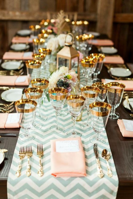 a chevron mint table runner, peachy napkins and gold flatware and gold rimmer glasses
