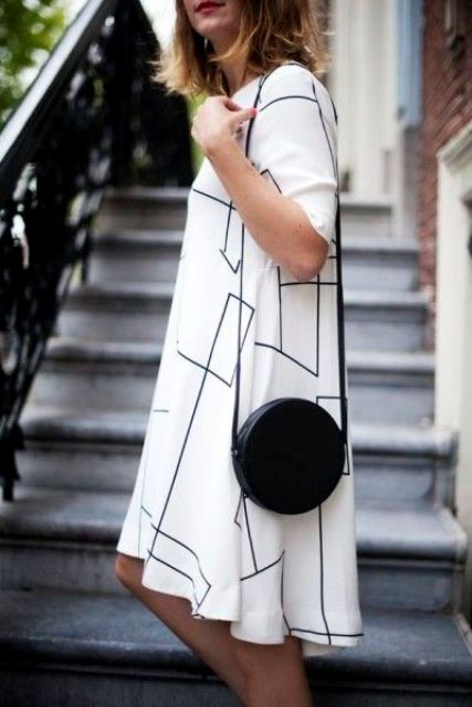 a black round crossbody bag adds interest to the monochrome outfit