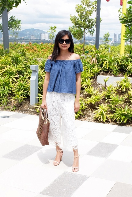 With blue off the shoulder shirt, white heels and tote