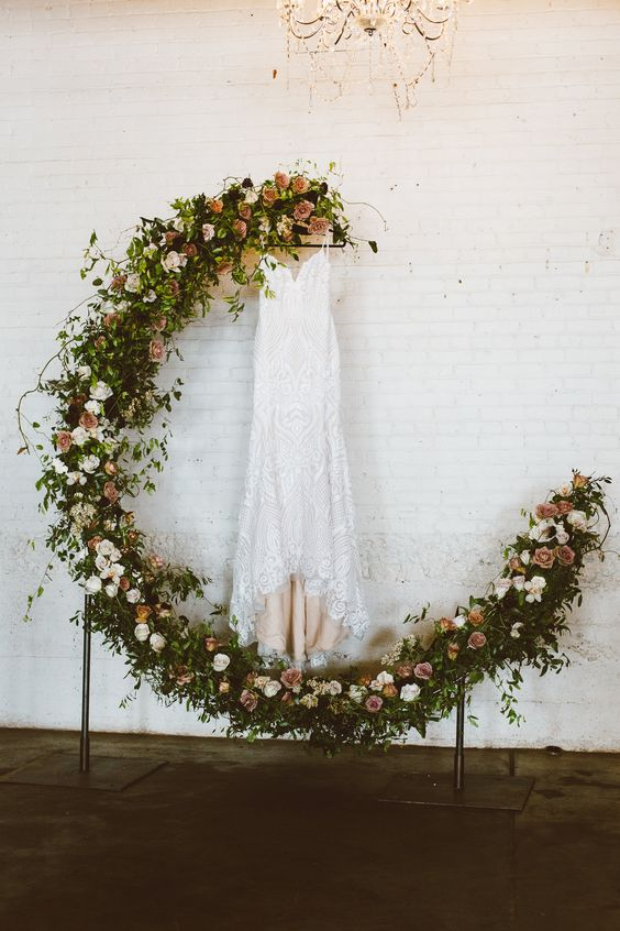 a dreamy crescent moon wedding arch made fully of greenery and fresh blooms is a gorgeous idea
