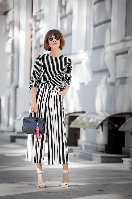 With striped shirt, white sandals and black mini bag