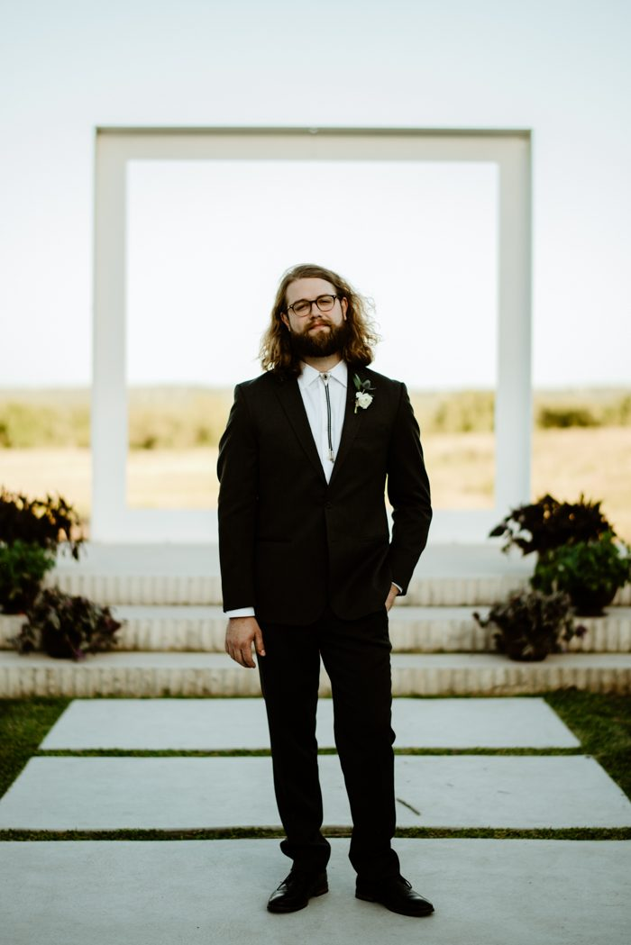 The groom was wearing a tailored suit with a bolo tie and glasses, he looked rather boho chic