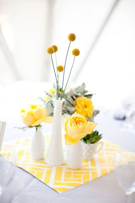 a wedding centerpiece with a printed napkin, yellow blooms and pale miller in white vases