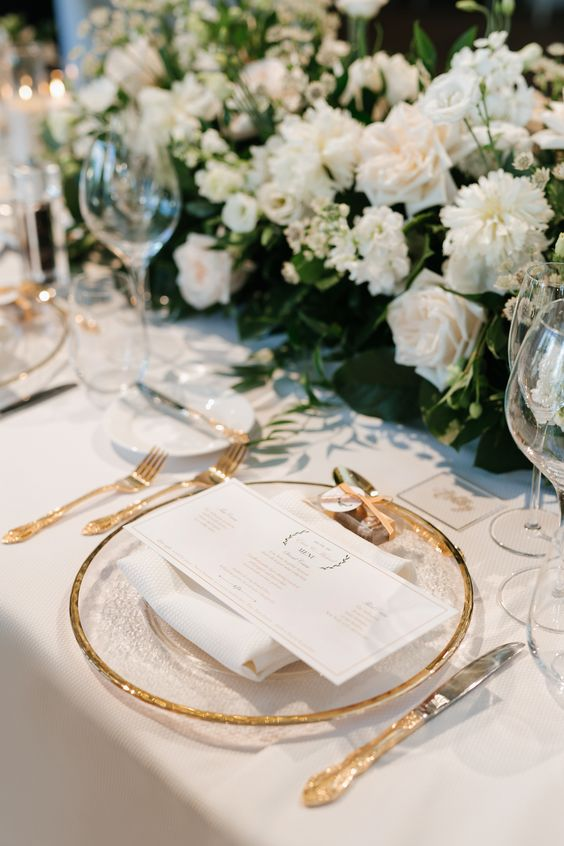 a modern and elegant table setting with lush white and blush blooms and gold touches