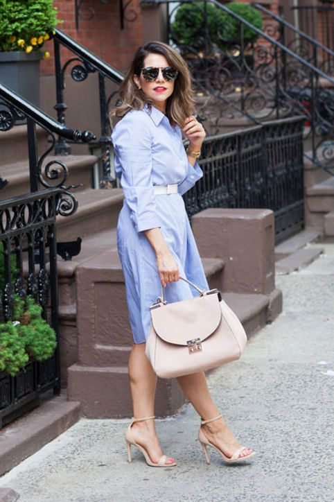 a blue shirtdress with a white belt, nude heels and a blush bag for a comfy office look