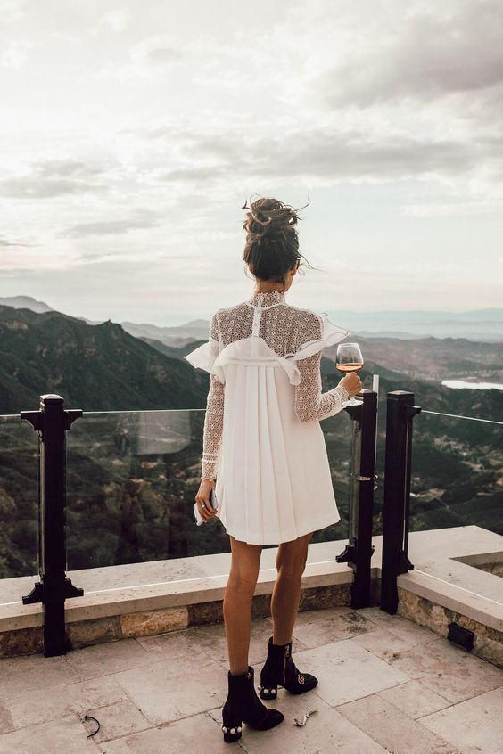 a mini dress with a lace bodice and a pleated skirt, black booties with badges for a boho off-beat bride