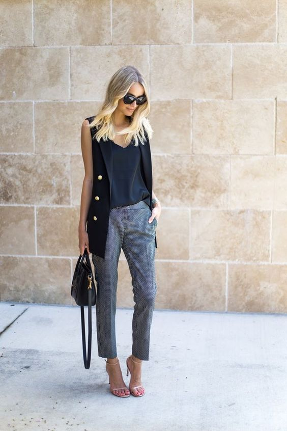 a black top and long vest with gold buttons and printed cropped pants, nude shoes and a black bag