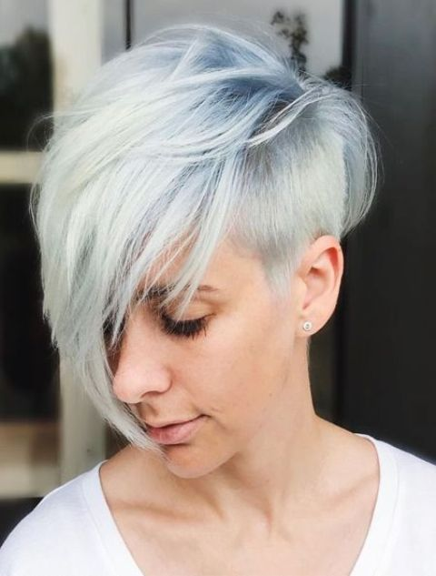 a longer pixie haircut with a side fringe and a chic blue to white balayage