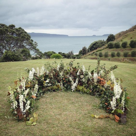 a textural fall wedding altar with white blooms, much foliage and herbs and dark leaves adds interest and dimension