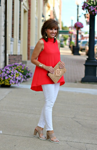 With white pants, gray sandals and clutch