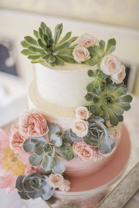 an ombre wedding cake with blush blooms and succulents for decor