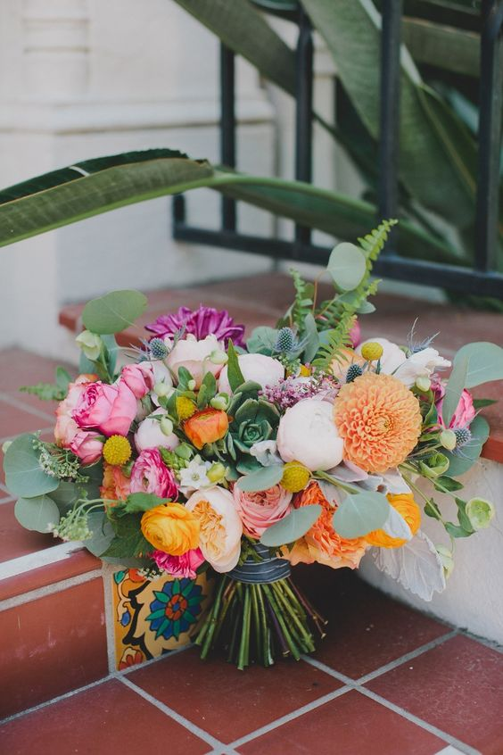 a colorful bouquet with purple, pink, orange and blush blooms and lots of ferns and eucalyptus