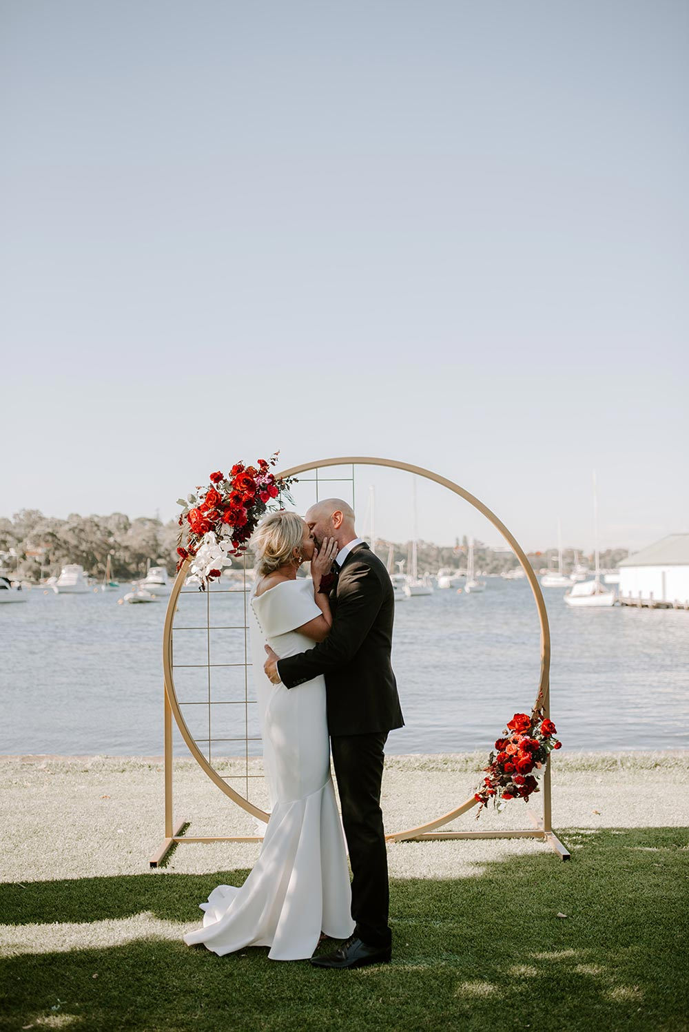 modern circular wedding ceremony backdrop with red flowers