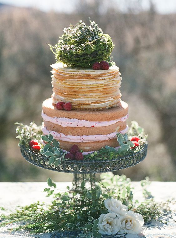 a naked partly pancake wedding cake with raspberries decorated with greenery is a catchy idea