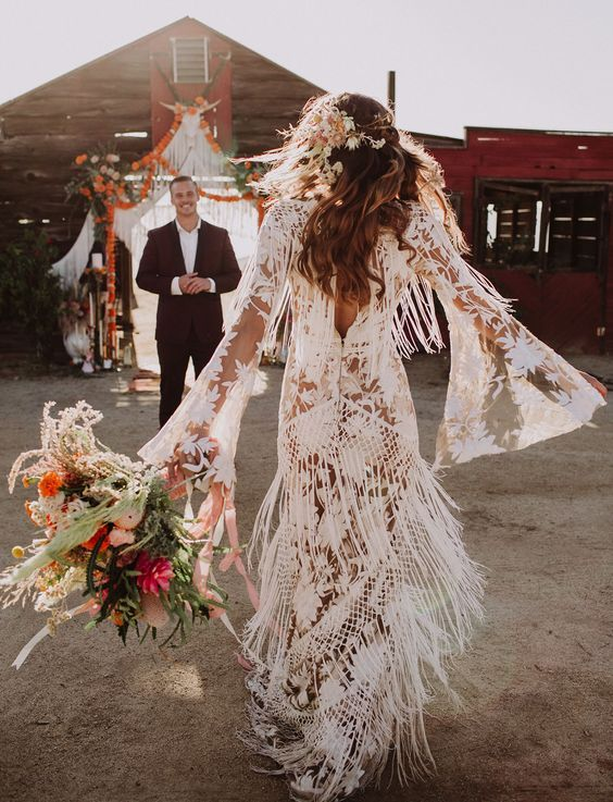 a boho lace wedding dress with bell sleeves and fringe for a free-spirited feel