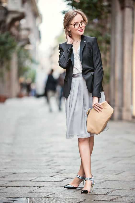 a grey knee skirt, a white shirt, a black jacket, a tan clutch and catchy kitten heels
