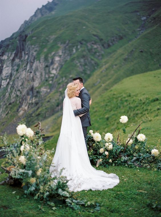 an organic greenery and white blooms outdoor wedding altar helps to enjoy the highlands around