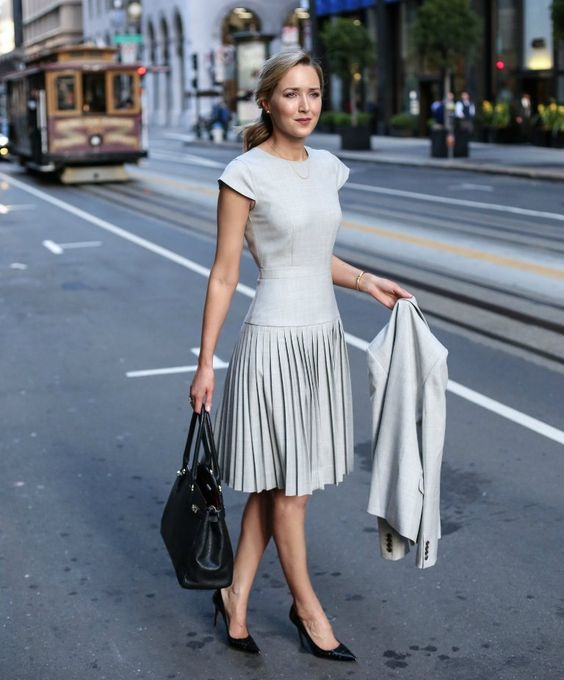 a light grey A-line dress with cap sleeves, a pleated skirt and a macthing jacket