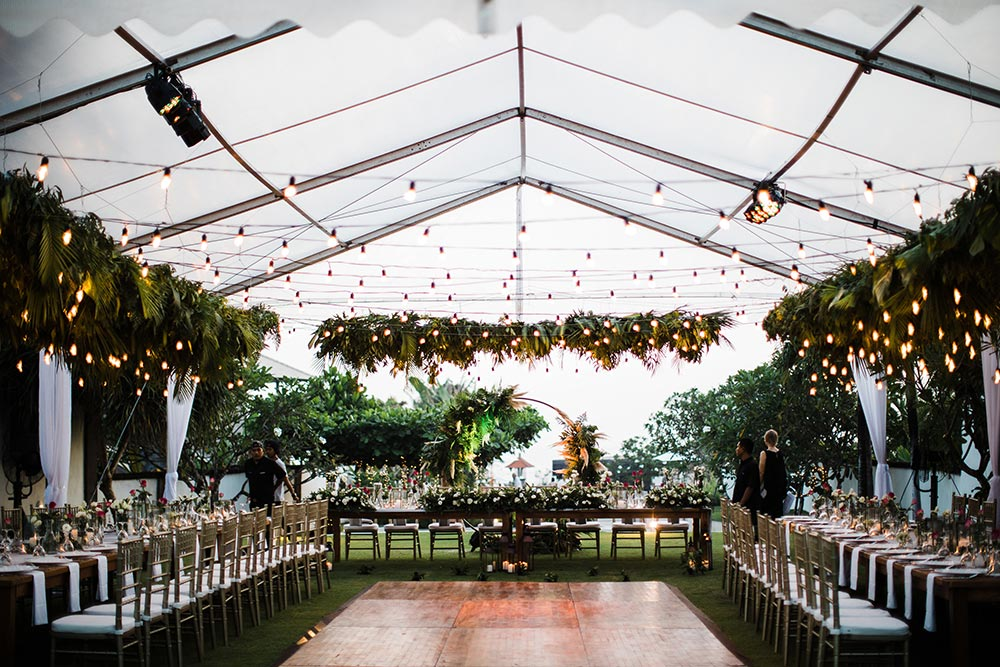 tropical wedding reception tablescape with palm frond ceiling and bistro lights