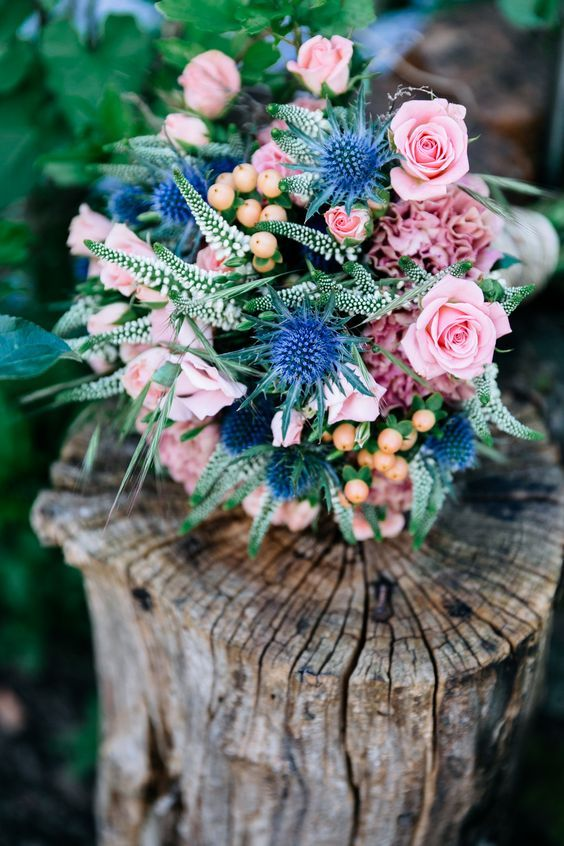 a cute bouquet with blue thistles, soft pink garden roses and some greenery for a sweet summer look