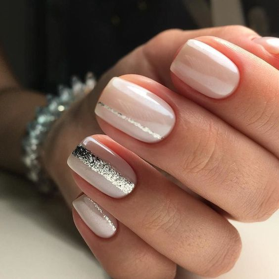 creamy nails with silver glitter stripes on some of them for a modern romantic look