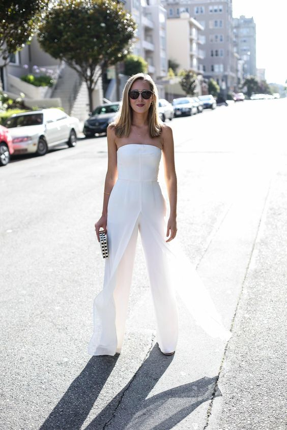 a white strapless jumpsuit with culottes and an overskirt, sandals and a printed clutch for a minimalist or modern bride