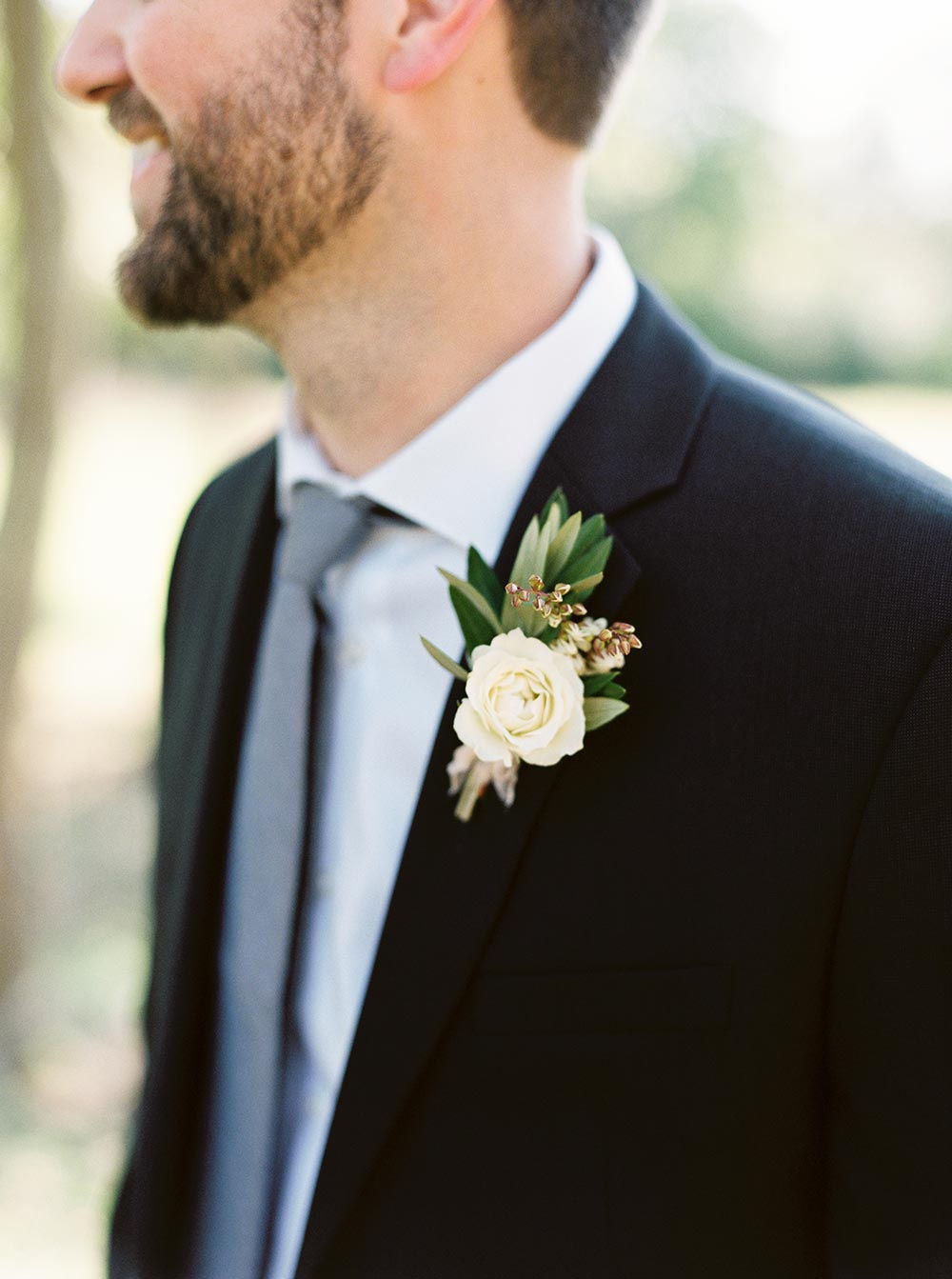 black groom suit with cream boutonniere