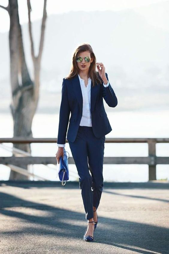 a navy pantsuit, a white button down, navy shoes and a bold blue bag