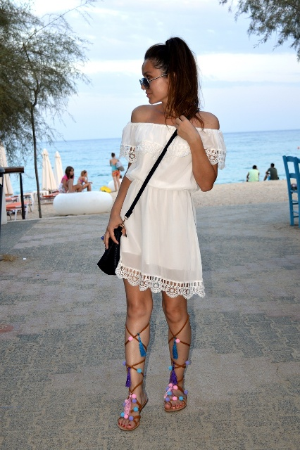 With white lace dress and black bag