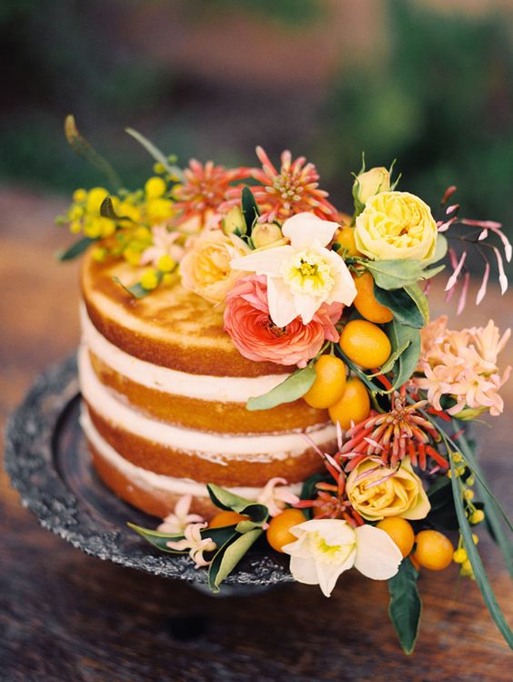 a naked wedding cake topped with yellow, pink and white blooms and kumquats for a Mediterranean wedding
