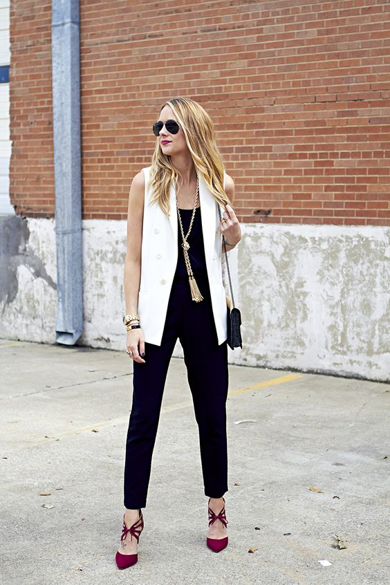a black jumpsuit, a white long vest, red lace up shoes, a tassel necklace and a black bag