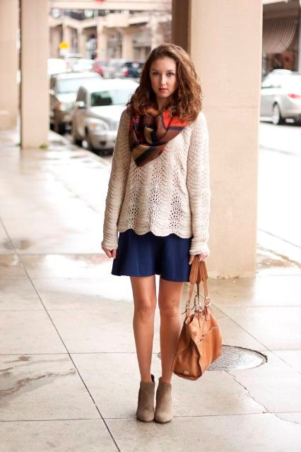 With navy blue skirt, printed scarf, gray ankle boots and brown bag